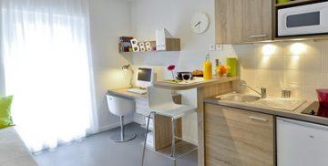 un petit studio avec une petite cuisine